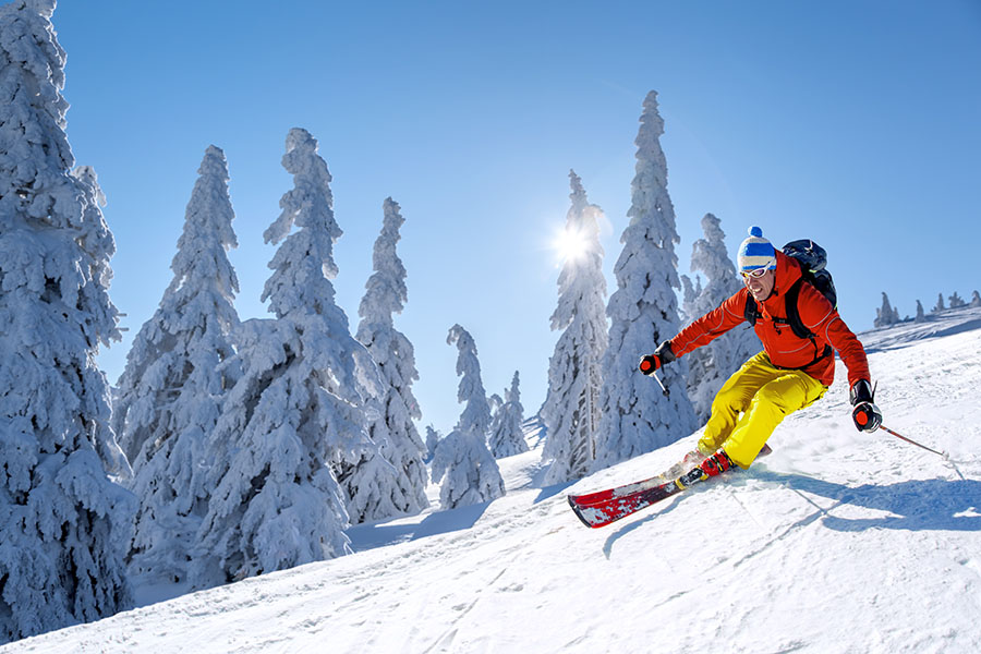Travel Insurance - View of Man Skiing Down Snowy Mountain in the Alps